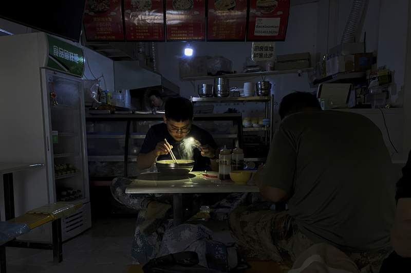 FILE - In this Sept. 29, 2021, file photo, a man uses his smartphone flashlight to light up his bowl of noodles as he eats his breakfast at a restaurant during a blackout in Shenyang in northeastern China's Liaoning Province. Chinese officials on Wednesday, Oct. 13, 2021 said they can ensure homes in the countrys north will be heated during the winter amid a nationwide electricity crunch that has brought power cuts in some areas.  (AP Photo/Olivia Zhang, File)