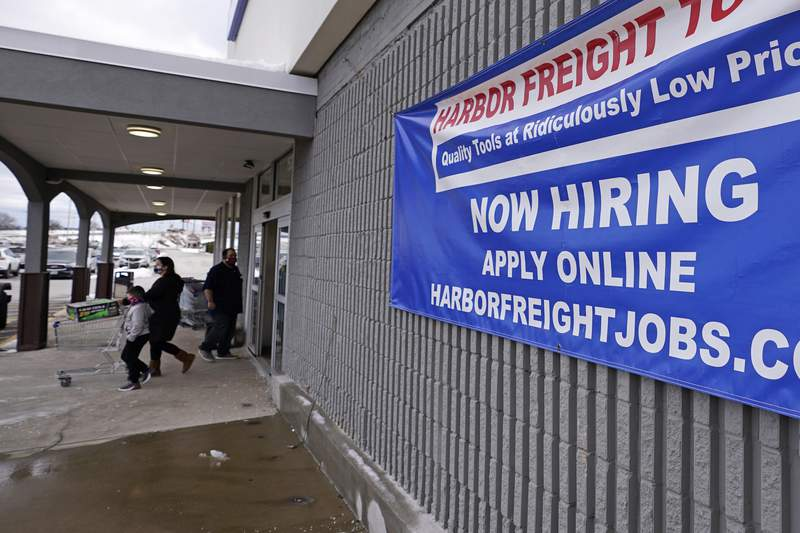 "FILE - In this Dec. 10, 2020 file photo, a ""Now Hiring"" sign hangs on the front wall of a Harbor Freight Tools store in Manchester, N.H.   U.S. employers cut back sharply on hiring in December, particularly in pandemic-hit industries such as restaurants and hotels, as soaring virus infections and government restrictions weakened the economy that month. The number of available jobs rose slightly and layoffs fell, according to the Labor Departments Tuesday report, known as the Job Openings and Labor Turnover Survey, or JOLTS.  (AP Photo/Charles Krupa, File)"