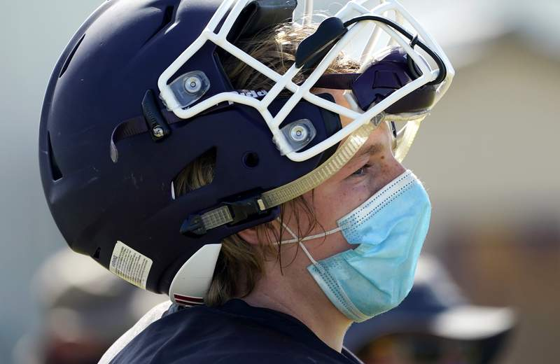 Thrall High School football player Hayden Stefek wears a face mask as he goes through a practice, Thursday, Aug. 13, 2020, in Thrall, Texas. Coronavirus testing in Texas has dropped significantly, mirroring nationwide trends, just as schools reopen and football teams charge ahead with plans to play. (AP Photo/Eric Gay)