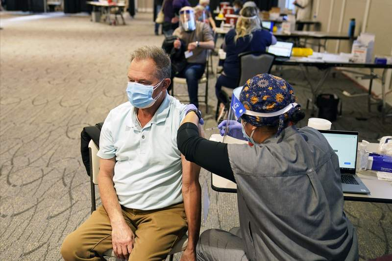 Ron Tupy receives a vaccination, Thursday, Jan. 21, 2021 at the Earle Brown Heritage Center in Brooklyn Center, Minn. (AP Photo/Jim Mone)