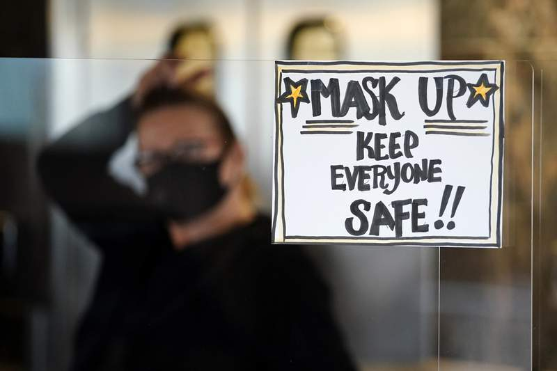 FILE - In this Tuesday, Nov. 17, 2020 file photo, manager Yllka Murati waits for a delivery driver to pick up takeout orders behind a partition displaying a sign to remind customers to wear a mask, at the Penrose Diner, in south Philadelphia. (AP Photo/Matt Slocum, File)