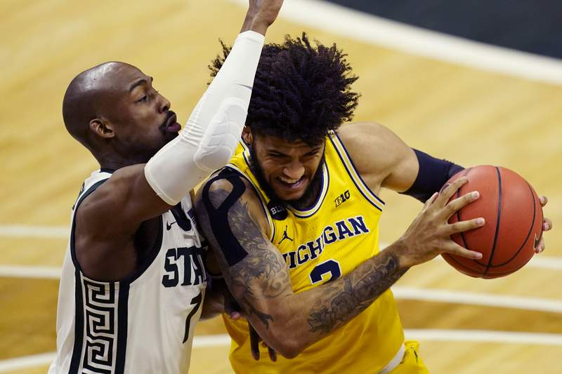Michigan forward Isaiah Livers (2) is defended by Michigan State guard Joshua Langford (1) during the first half of an NCAA college basketball game, Sunday, March 7, 2021, in East Lansing, Mich. (AP Photo/Carlos Osorio)