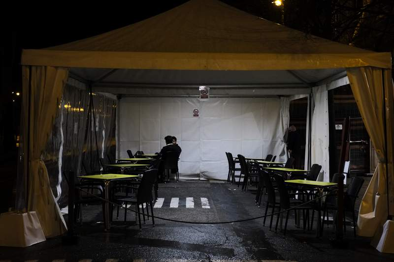 Two persons seated in a terrace close to service tables empty by new measures to prevent the spread of the coronavirus, in Pamplona, northern Spain, Thursday, Jan. 27, 2021. (AP Photo/Alvaro Barrientos)