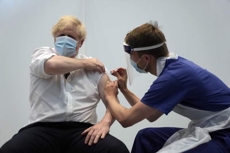 British Prime Minister Boris Johnson receives his second jab of the AstraZeneca coronavirus vaccine from James Black, at the Francis Crick Institute in London, Thursday, June 3, 2021. (AP Photo/Matt Dunham, Pool)