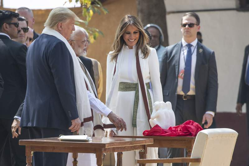 U.S. President Donald Trump, with first lady Melania Trump, look at gift from Indian Prime Minister Narendra Modi, as they tour Gandhi Ashram, Monday, Feb. 24, 2020, in Ahmedabad, India. (AP Photo/Alex Brandon)