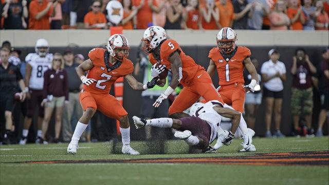 Running back Justice Hill #5 of the Oklahoma State Cowboys is tripped up by cornerback Zack Sanders #26 of the Missouri State Bears at Boone Pickens Stadium on August 30, 2018 in Stillwater, Oklahoma. The Cowboys defeated the Bears 58-17. (Photo by Brett Deering/Getty Images)