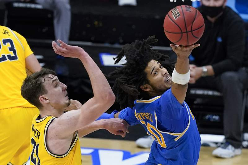 UCLA guard Tyger Campbell drives to the basket in front of Michigan guard Franz Wagner, left, during the second half of an Elite 8 game in the NCAA men's college basketball tournament at Lucas Oil Stadium, Tuesday, March 30, 2021, in Indianapolis. (AP Photo/Darron Cummings)