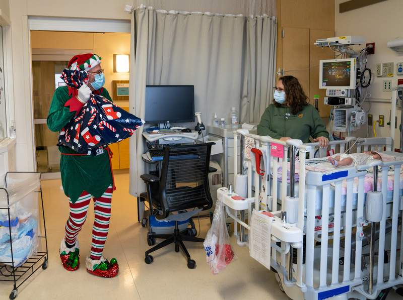A member of the Mott Child and Family Life team dressed as an elf delivers presents to a pediatric patient at Mott Children's Hospital.