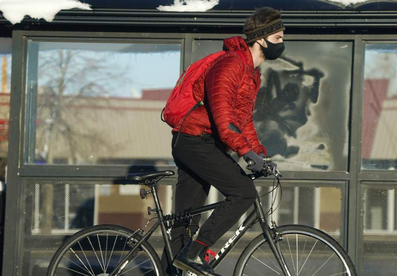 A cyclist wears a face mask while riding on a trail after more than a foot of snow was left by a late winter storm that swept over the region Thursday, Feb. 25, 2021, in Boulder, Colo. (AP Photo/David Zalubowski)