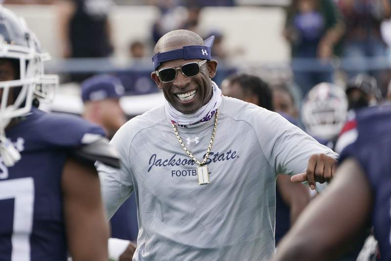 FILE - In this March 14, 2021, file photo, Jackson State football coach Deion Sanders smiles as he greets his defensive squad after they had recovered a Mississippi Valley State fumble for a touchdown during the second half of an NCAA college football game in Jackson, Miss. Sanders connections helped his Tigers get uniforms by Under Armour with Walmart assisting with a new turf field. (AP Photo/Rogelio V. Solis, File)
