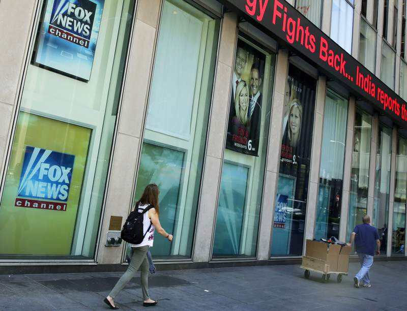 FILE- People pass the News Corporation headquarters building and Fox News studios in New York on Aug. 1, 2017.  New York City's human rights commission has fined Fox News $1 million for violation of laws protecting against sexual harassment and job retaliation. It's the largest such penalty in the commission's history.  (AP Photo/Richard Drew, File)