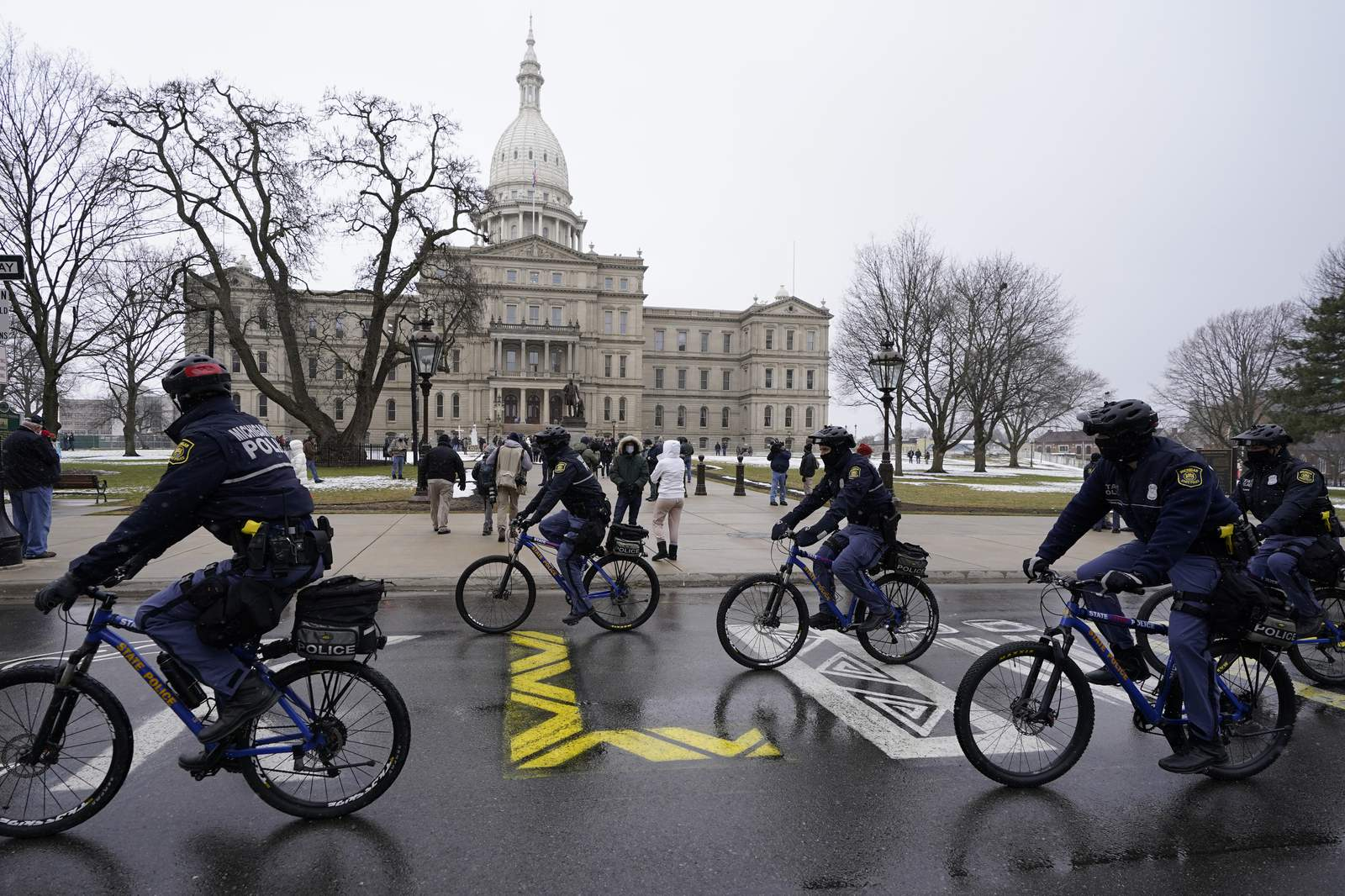 Michigan State Police patrol the perimeter of the State Capitol, Sunday, Jan. 17, 2021, in Lansing, Mich. (AP Photo/Carlos Osorio)