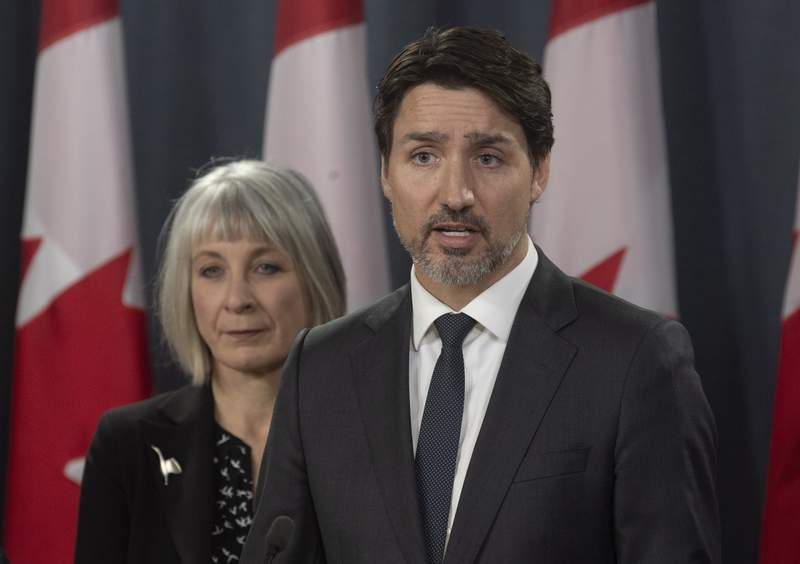 Minister of Health Patty Hajdu looks on as Prime Minister Justin Trudeau speaks during a news conference  in Ottawa, Wednesday March 11, 2020.  Canada is announcing $1 billion ($730 million) in funding to help health-care workers cope with the increasing number of new cases of coronavirus and to help Canadian workers who are forced to isolate themselves.  (Adrian Wyld/The Canadian Press via AP)