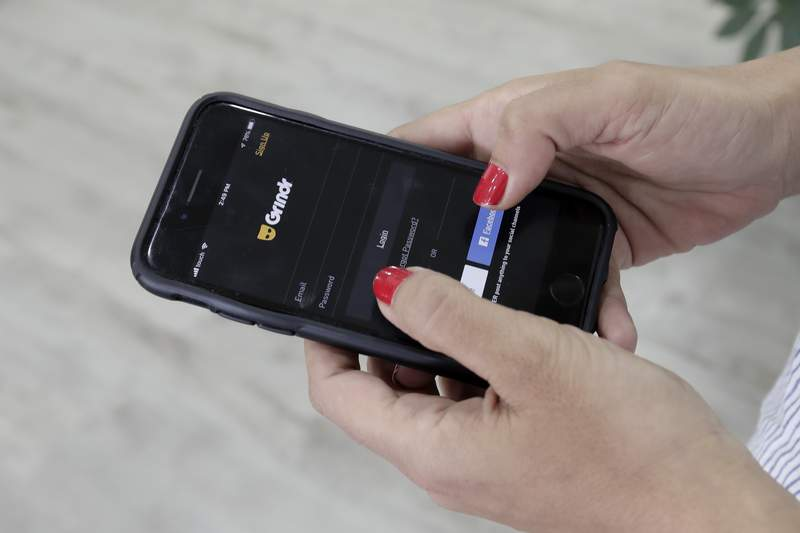 FILE - In this Wednesday, May 29, 2019 file photo, a woman checks the Grindr app on her mobile phone in Beirut, Lebanon. Dating apps including Grindr, OkCupid and Tinder leak personal information to advertising tech companies in possible violation of European data privacy laws, a Norwegian consumer group said in a report Tuesday, Jan. 14, 2020. The Norwegian Consumer Council said it found serious privacy infringements in its analysis of how shadowy online ad companies track and profile smartphone users. (AP Photo/Hassan Ammar, file)