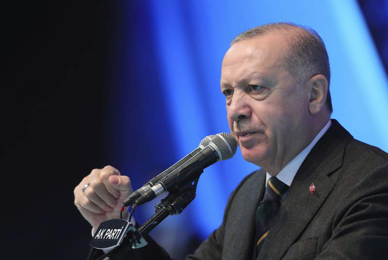 FILE - In this file photo dated Wednesday, March 24, 2021, Turkey's President Recep Tayyip Erdogan gestures as he delivers a speech during his ruling party's congress inside a packed sports hall in Ankara, Turkey.  Libya's visiting interim prime minister and Turkish President Recep Tayyip Erdogan affirmed their commitment to a controversial maritime demarcation agreement, Monday April 12, 2021, that has angered Greece and Cyprus. (Turkish Presidency via AP, FILE)