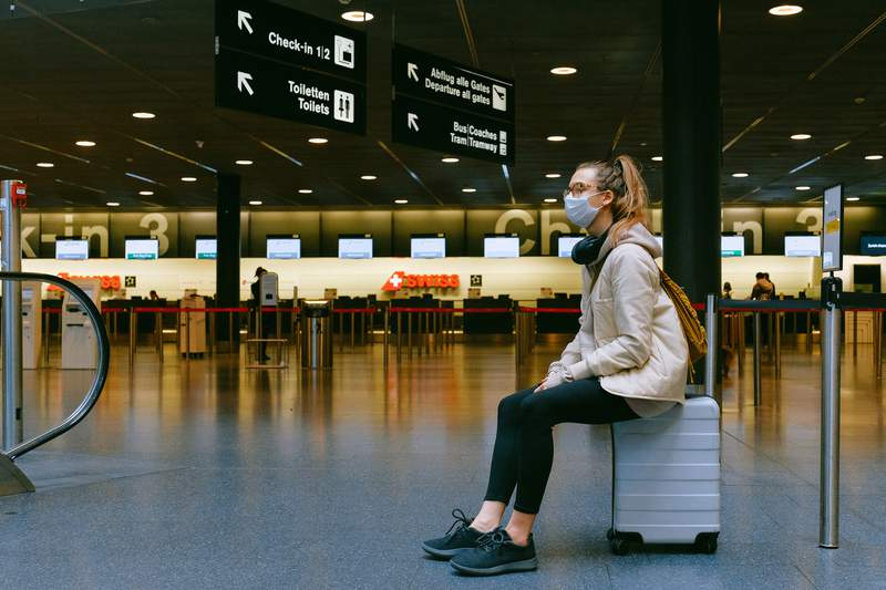 A woman waits for luggage at the airport.