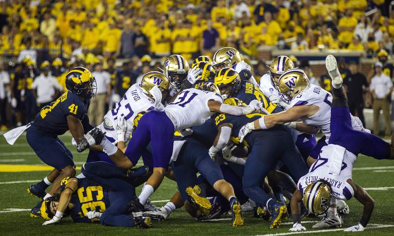 Michigan linebacker Michael Barrett (23) rushes with a fake punt to convert on a fourth down in the second quarter of an NCAA college football game against Washington in Ann Arbor, Mich., Saturday, Sept. 11, 2021. (AP Photo/Tony Ding)