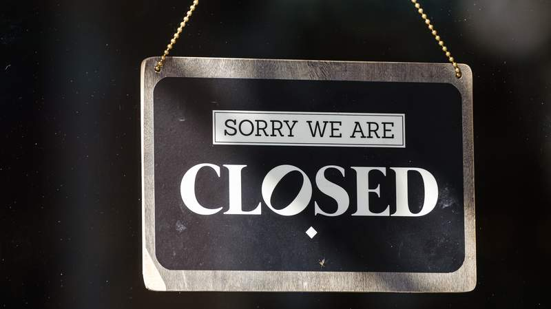 """A """"closed"""" sign outside a business."""