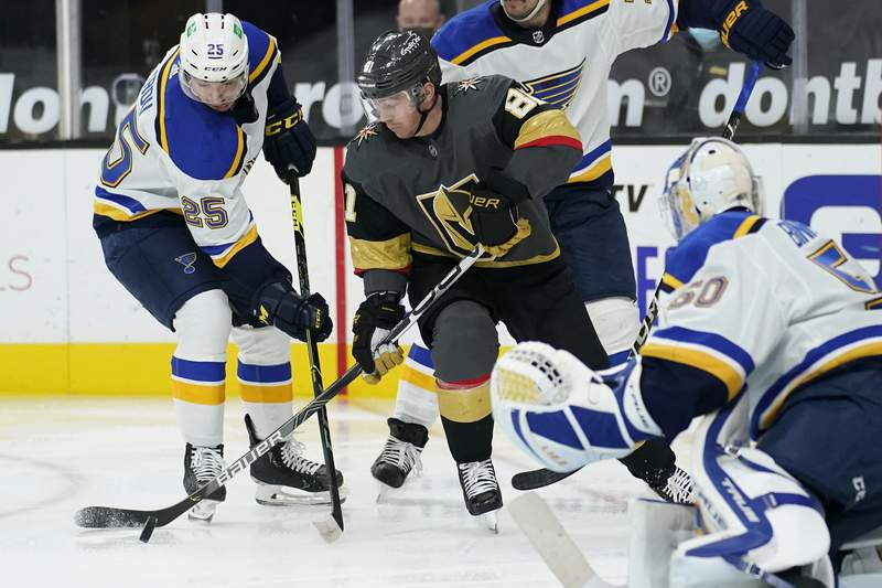 St. Louis Blues center Jordan Kyrou (25) and Vegas Golden Knights center Jonathan Marchessault (81) vie for the puck during the second period of an NHL hockey game Tuesday, Jan. 26, 2021, in Las Vegas. (AP Photo/John Locher)