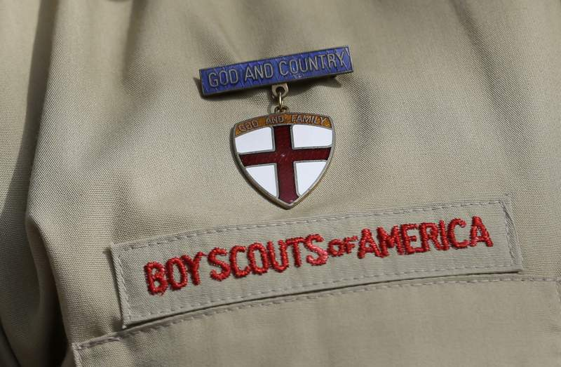 FILE - In this Feb. 4, 2013 file photo, shows a close up detail of a Boy Scout uniform worn during a news conference in front of the Boy Scouts of America headquarters in Irving, Texas. The committee representing child sex abuse survivors in the Boy Scouts of America bankruptcy case has agreed to the extension of an injunction halting lawsuits against local Boy Scouts councils and sponsoring organizations. In return for the extension, the BSA and local councils must provide the committee with information about local troop rosters that can help victims validate their claims, according to a court filing submitted Monday, March 8, 2021.  (AP Photo/Tony Gutierrez, File)