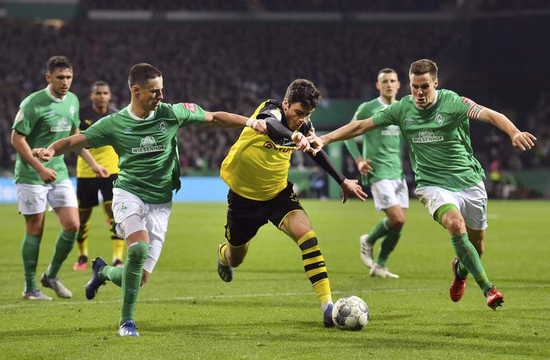 Dortmund's Giovanni Reyna, middle, moves the ball against Werder's Marco Friedl, left, and Niklas Moisander, right, during a soccer game, Tuesday, Feb. 4, 2020 in Bremen, Germany. (David Hecker/dpa via AP)