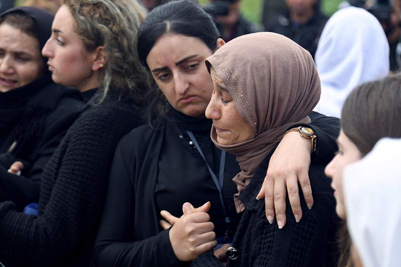 FILE - In this March 15, 2019 file photo, Iraqi Yazidi women grieve during the exhumation process of a mass grave in Iraq's northwestern region of Sinjar. U.N. investigators have collected millions of call data records implicating Islamic State militants in atrocities committed in northern Iraq, but delays in passing a law to govern war crimes probes is hindering the pursuit of justice, according to the head of the investigation. The data will help geolocate suspects in and around Sinjar in the summer of 2014, when the extremists killed and enslaved thousands of Yazidis.  (AP Photo/Farid Abdulwahed, File)