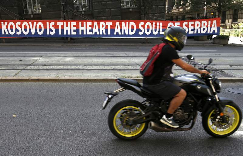 A motorcyclist rides past a billboard reading: ''Kosovo is the heart and soul of Serbia'' placed on a street in front of the government building in Belgrade, Serbia, Wednesday, Sept. 2, 2020. Serbian President Aleksandar Vucic and Kosovo Prime Minister Avdullah Hoti will meet at the White House on Thursday and Friday. (AP Photo/Darko Vojinovic)