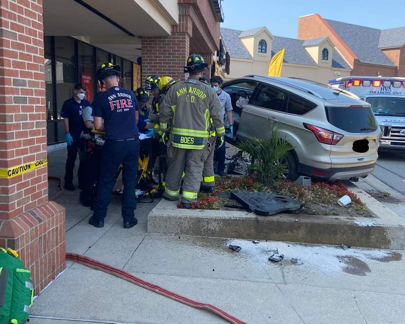 Ann Arbor firefighters and members of Huron Valley Ambulance are seen responding to a single-vehicle crash at Traver Village Shopping Center on July 26, 2021.