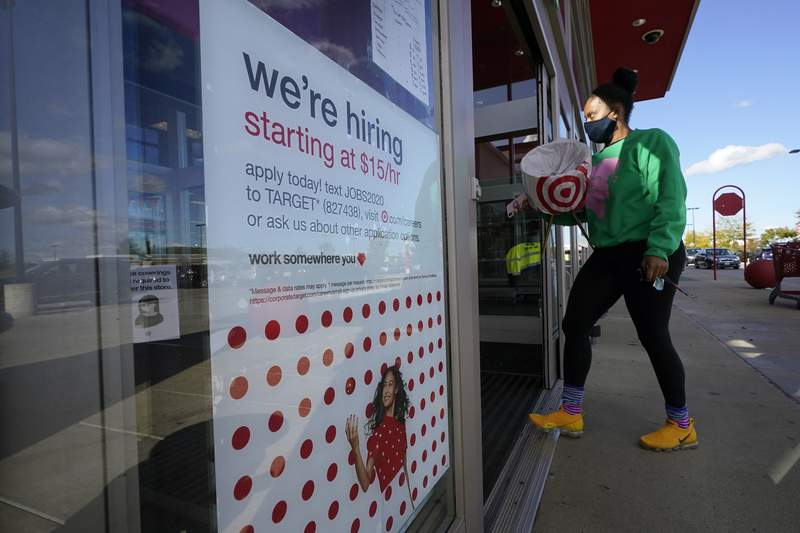 FILE - In this Sept. 30, 2020, file photo, a passerby walks past a hiring sign while entering a Target store in Westwood, Mass.  (AP Photo/Steven Senne, File)