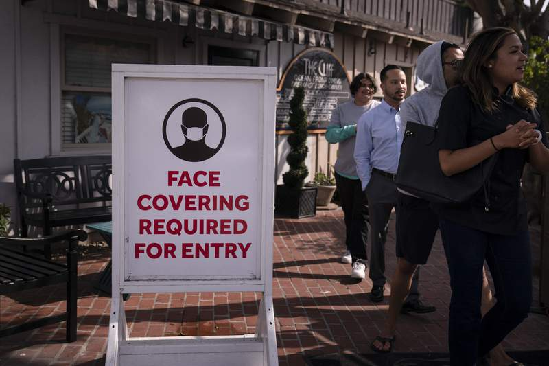 FILE - In this May 17, 2021, file photo, people walk past a sign requesting customers to wear masks in Laguna Beach, Calif. Federal health officials new, more relaxed recommendations on masks have all but eclipsed another major change in guidance from the government: Fully vaccinated Americans can largely skip getting tested for the coronavirus. (AP Photo/Jae C. Hong, File)
