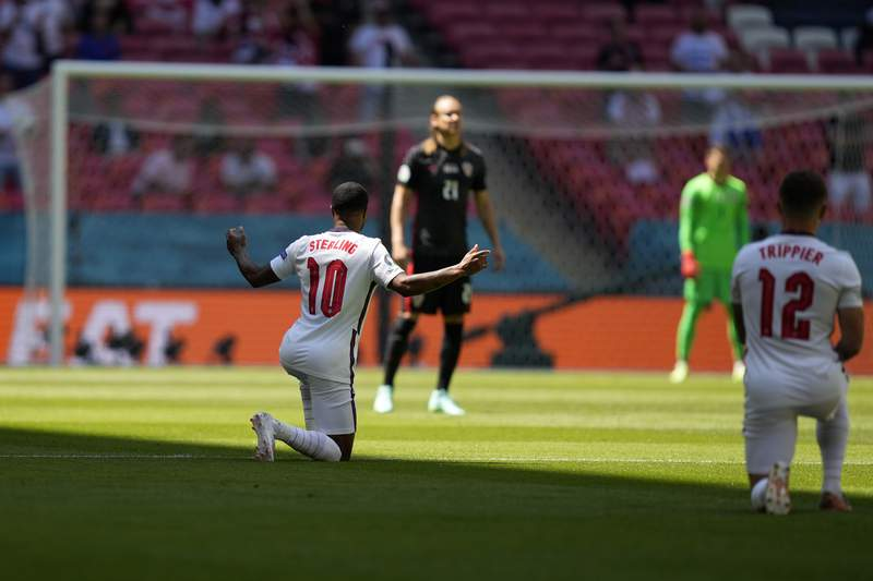 England's Raheem Sterling, left, takes the knee before the start of the Euro 2020 soccer championship group D match between England and Croatia at Wembley stadium in London, Sunday, June 13, 2021. (AP Photo/Frank Augstein, Pool)