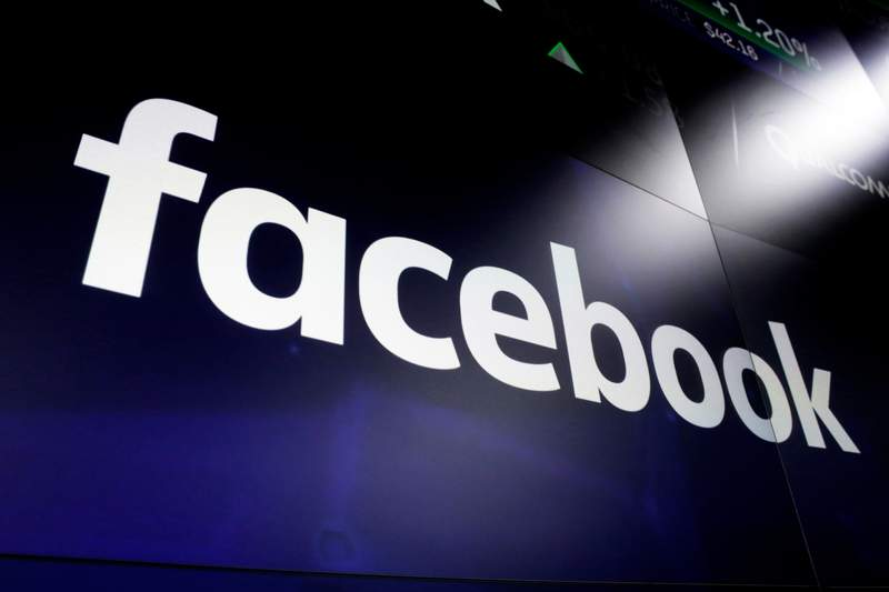 FILE - In this March 29, 2018, file photo, is the logo for social media giant Facebook at the Nasdaq MarketSite in New York's Times Square. Facebook has removed more than 275 accounts that used fake profile to pose as conservative Americans. The platform announced Thursday, Oct. 8, 2020, that it's also banned an Arizona-based marketing firm that its investigation found was behind the fake accounts. (AP Photo/Richard Drew, File)