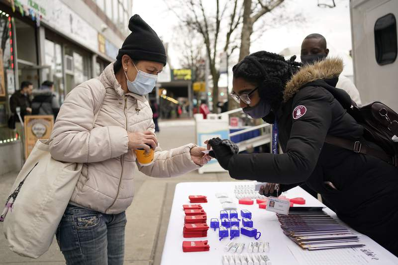 Research recruitment specialist Cristina Barron, right, talks with a pedestrian passing by a mobile medical van parked in the Queens borough of New York, Tuesday, Jan. 5, 2021. With more vaccines in the pipeline, scientists worry whether enough volunteers will join and stick with the testing needed to prove if they, too, really work. To help, researchers in more than a dozen spots around the country are rolling out mobile health clinics to better reach minority participants and people in rural areas who might not otherwise volunteer. (AP Photo/Seth Wenig)