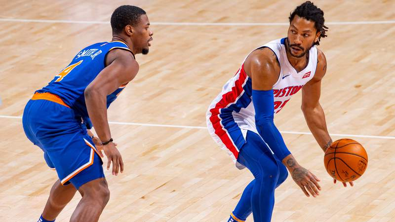 Derrick Rose #25 of the Detroit Pistons moves the ball up court in front of Dennis Smith Jr. #4 of the New York Knicks in the second half of an NBA game at Little Caesars Arena on December 13, 2020 in Detroit, Michigan.