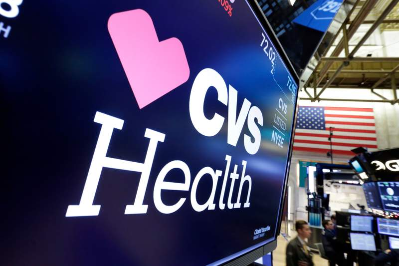 FILE- In this Dec. 4, 2017, file photo, the CVS Health logo appears above a trading post on the floor of the New York Stock Exchange.  CVS Healths second-quarter performance beat Wall Streets expectations as the drugstore chain and pharmacy benefits manager experienced reduced benefit costs. It raised its full-year earnings forecast. (AP Photo/Richard Drew, File)