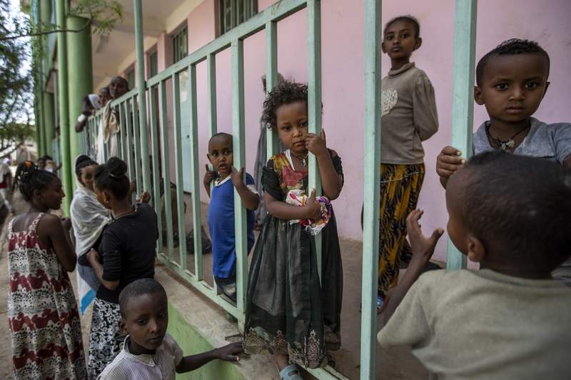 Children displaced by the conflict play on metal railings at the elementary school where they now live with their families in the town of Abi Adi, in the Tigray region of northern Ethiopia Tuesday, May 11, 2021. (AP Photo/Ben Curtis)
