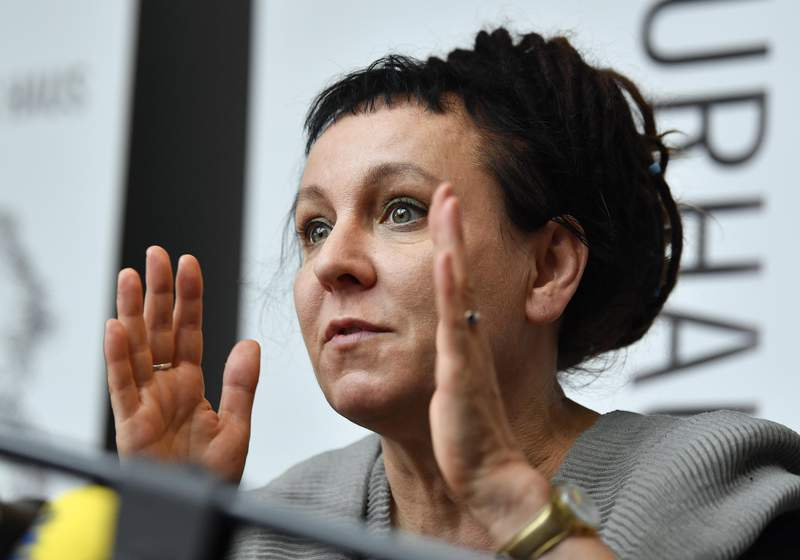 FILE - In this Friday, Oct. 11, 2019 file photo, Polish writer and Nobel Prize winner Olga Tokarczuk reacts to the media during a press conference in Duesseldorf, Germany. Nobel Prize-winning writer Olga Tokarczuk has declined an honorary citizenship from the region of Poland where she lives because she would have had to share the honor with a Roman Catholic bishop who has made hostile comments about the LGBT community. Tokarczuk said in a tweet Friday, Sept. 25 that while she appreciated being considered, she sadly couldnt accept Lower Silesias honorary citizenship. (AP Photo/Martin Meissner, file)