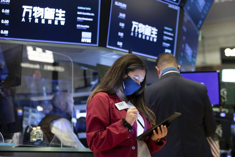 In this photo provided by the New York Stock Exchange, trader Ashley Lara works on the trading floor, Friday, June 11, 2021. Stocks were broadly lower Friday after a Federal Reserve official said that the nation's central bank might need to raise interest rates as early as next year, sooner than the Fed's latest estimate of possible rate increases in 2023. (Nicole Pereira/New York Stock Exchange via AP)