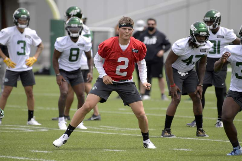 FILE - New York Jets first round draft pick Zach Wilson works out during NFL rookie camp in Florham Park, N.J., in this Friday, May 7, 2021, file photo. The New York Jets and quarterback Zach Wilson have agreed to terms on his four-year rookie contract, according to a person with direct knowledge of the deal. Wilson, the No. 2 overall pick in the NFL draft in April, missed the first two days of training camp practices while the two sides hammered out details. (AP Photo/Bill Kostroun, File)