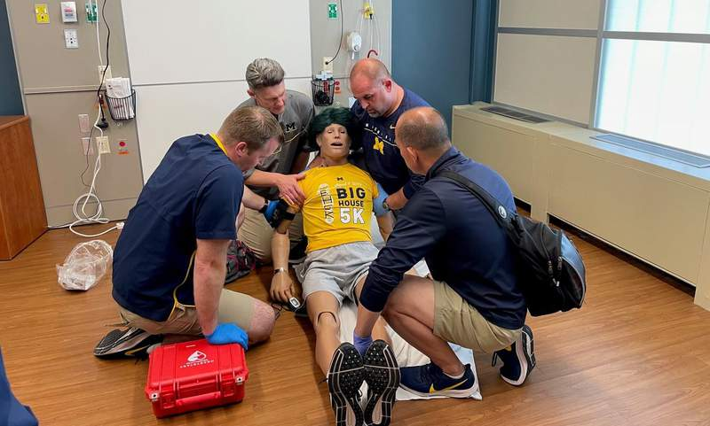 U of M athletic medicine professionals are guided through a scenario from a simulation control room.