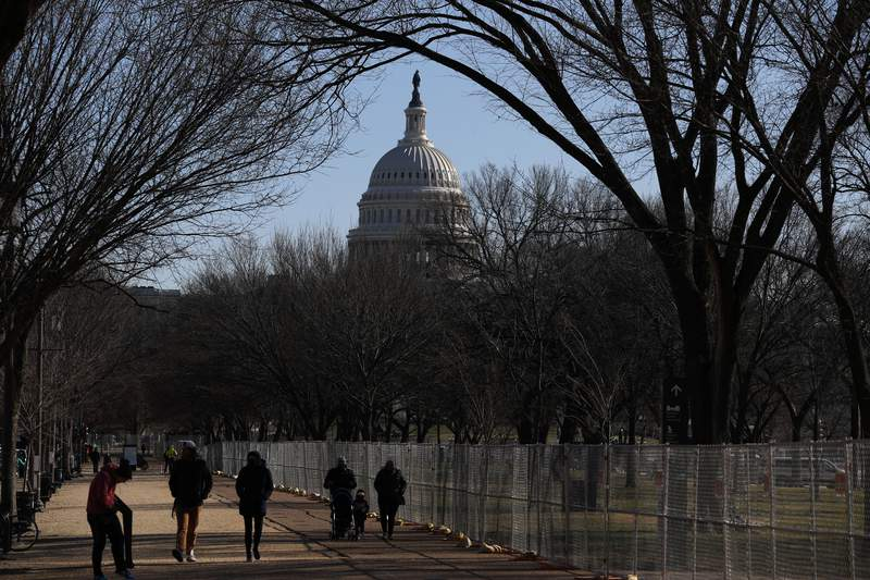 People stroll past a section of the National Mall by the Capitol where workers were still dismantling inauguration installations, after most downtown streets and public spaces had reopened to the public, on Saturday, Jan. 23, 2021 in Washington. Biden is looking to jump-start his first 100 days in office with action and symbolism to reassure a divided and weary public that help is in the offing. (AP Photo/Rebecca Blackwell)