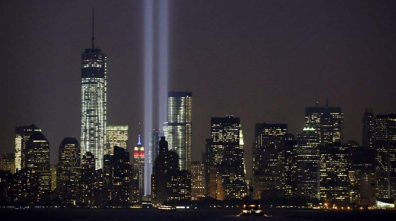 In this Wednesday, Sept. 11, 2013, file photo, the twin beams of the annual Tribute in Light commemorating the Sept. 11, 2001, terrorist attacks shine amid the city's skyline, in New York. The twin beams of light representing the World Trade Center towers won't be beamed into the sky during the 2020 memorial of the 9/11 terror attacks in New York City, because of concerns about the coronavirus and the health of work crews. (AP Photo/Kathy Willens, File)