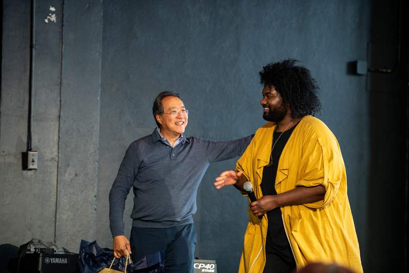 """Yo-Yo Ma (left) and Tunde Olaniran on stage during his """"Day of Action"""" in Flint, Michigan in Feb. 2019, organized in partnership with the University of Michigan's University Musical Society."""