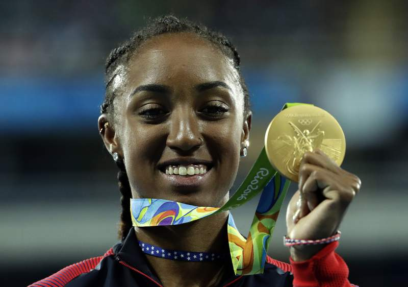 FILE - In this Thursday, Aug. 18, 2016 file photo, Gold medal winner Brianna Rollins from the United States shows off her medal during the medal ceremony for the women's 100-meter hurdles final during the athletics competitions of the 2016 Summer Olympics at the Olympic stadium in Rio de Janeiro, Brazil. Brianna Rollins-McNeal has been banned for five years in a doping case it was reported on Friday, June 4, 2021. The decision rules her out of this year's Tokyo Games and the 2024 Paris Games. The Athletics Integrity Unit says the Americans second career ban was for tampering within the results management process of doping control samples. The 29-year-old hurdler's ban runs to August 2024. AP Photo/Dmitri Lovetsky, File)