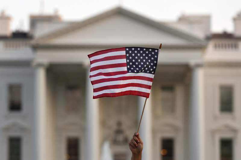 FILE - In this Sept. 2017 file photo, a flag is waved outside the White House, in Washington.  The Trump administration announced Friday that it was curbing legal immigration from six additional countries that officials said did not meet security screening standards, as part of an election-year push to further restrict immigration. Officials said immigrants from Kyrgyzstan, Myanmar, Eritrea, Nigeria, Sudan and Tanzania will face new restrictions in obtaining certain visas to come to the United States. But it is not a total travel ban, unlike President Donald Trumps earlier effort that generated outrage around the world for unfairly targeting Muslims. (AP Photo/Carolyn Kaster)