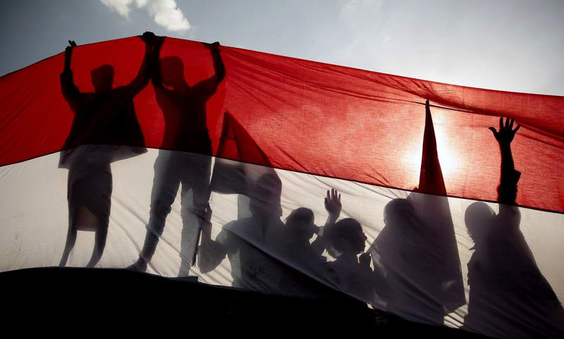 FILE - In this Sept. 26, 2016 file photo, men are silhouetted against a large representation of the Yemeni flag as they attend a ceremony to mark the anniversary of North Yemen's 1962 revolution in Sanaa, Yemen. On Monday, March 22, 2021, Saudi Arabia announced a plan to to offer Yemens Houthi rebels a cease-fire in the countrys yearslong war and allow a major airport to reopen in its capital. The Houthis offered no immediate comment to the proposal. (AP Photo/Hani Mohammed, File)