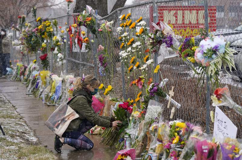 A mourner leaves a bouquet of flowers along a fence put up around the parking lot where a mass shooting took place in a King Soopers grocery store Tuesday, March 23, 2021, in Boulder, Colo. (AP Photo/David Zalubowski)