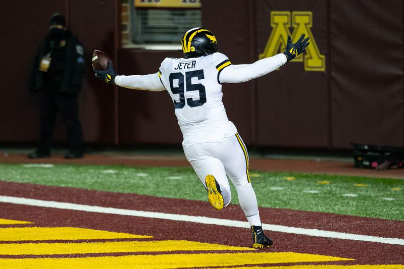 Donovan Jeter #95 of the Michigan Wolverines celebrates after scoring a touchdown after recovering a fumble by Tanner Morgan #2 of the Minnesota Golden Gophers (not pictured) in the first quarter of the game at TCF Bank Stadium on October 24, 2020 in Minneapolis, Minnesota.