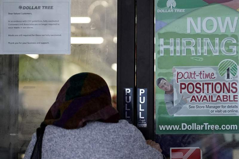 A shopper enters a retail store as a hiring sign shows in Buffalo Grove, Ill., Thursday, June 24, 2021.  Americas employers added 850,000 jobs in June, well above the average of the previous three months and a sign that companies may be having an easier time finding enough workers to fill open jobs. (AP Photo/Nam Y. Huh)