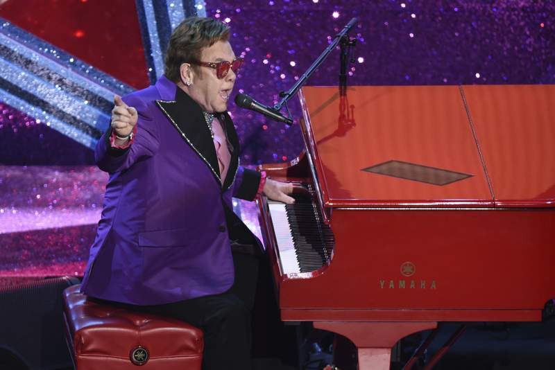 """FILE - In this Feb. 9, 2020, file photo, Elton John performs """"(I'm Gonna) Love Me Again,"""" nominated for the award for best original song, from """"Rocketman"""" at the Oscars in Los Angeles. John is opening up his vault and releasing an expansive collection of rarely heard and unreleased tracks. John announced Thursday, Sept. 17, 2020, that the eight-CD collection, Elton: Jewel Box,"""" will be released Nov. 13. The collection includes Sing Me No Sad Songs, an unreleased studio demo from 1969. (AP Photo/Chris Pizzello, File)"""